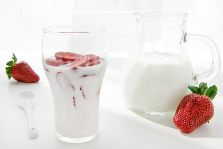 yogurt ice cream: Fresh yogurt with juicy strawberry slices in a glass on white Stock Photo