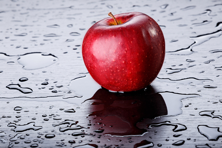 red apple on black background with water drops