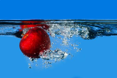 Red apple splashing in water with blue background Stock Photo
