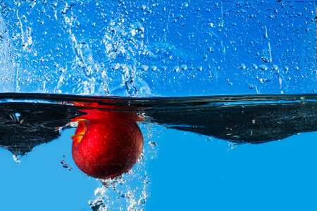 circular blue water ripple: Red apple splashing in water with blue background Stock Photo