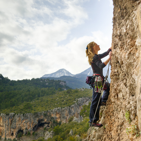 A young girl climber climbs high up the cliff in Geyikbayiri Tur