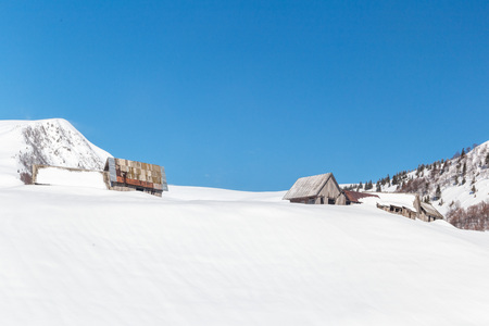 A small hut in front of a mountain covered in snow during the Ukrainian winter