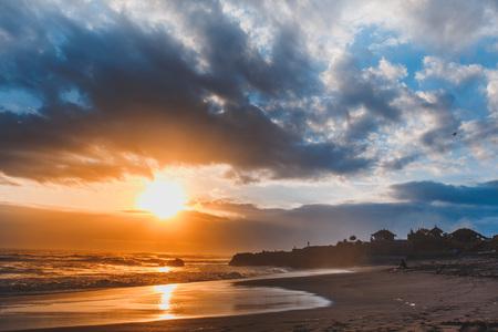 Sunset on black sand beach. Indian Ocean. Clody Sky. Bali Indonesia