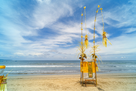 The penjor is a tall, curved bamboo pole decorated with coconut leaves with an offering at the base. Bali Indonesia. Foto de archivo
