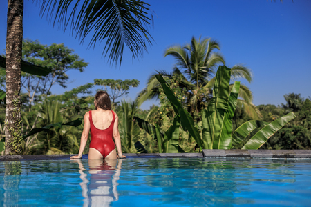 Woman in red swimsuit resting in the pool with a beautiful view of the palm trees on the island of Bali. Female in a private pool in Bali admires a beautiful view of the palm trees. Luxury holiday.