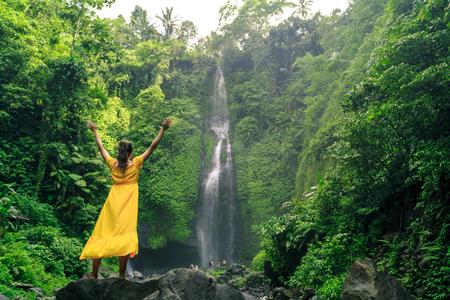 beautiful woman in yellow dress near waterfall wall