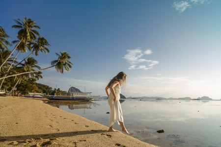 Woman standing on the sand in the El Nido beach, tasting the temperature of the water dipping her toe while on a summer holiday. Travel and outdoors lifestyle.