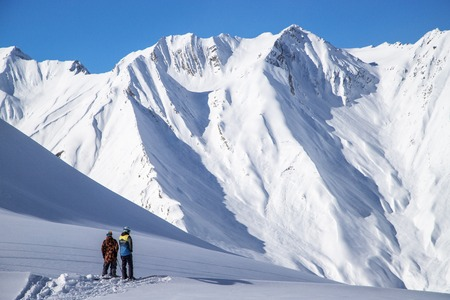Two skiers standing on top of freeride zone in Gudauri mountains, Georgia