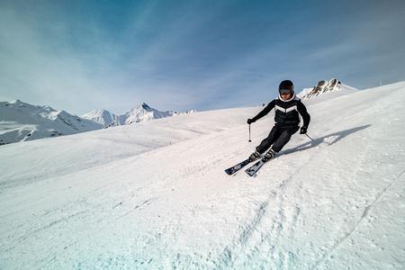 Männlicher Skifahrer Skifahren auf der Skipiste an einem sonnigen Wintertag im Skigebiet Gudauri in Georgia
