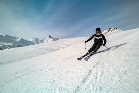 Male skier skiing on ski slope on a sunny winter day at the ski resort Gudauri in Georgia