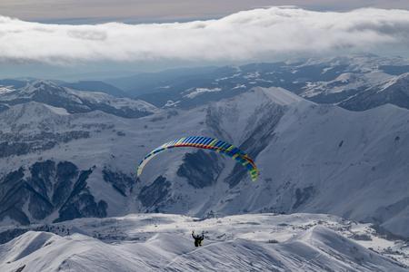 Paragliding at snowy mountains over ski resort at sunny winter day. Caucasus Mountains. Georgia, region Gudauri.