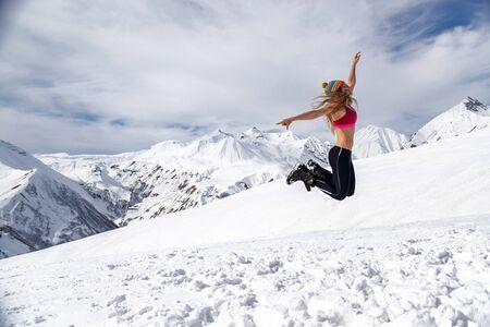 woman dressed in t-shirt jumping on the mountain peak with kavkazian snowy range and valley on the background. Freedom concept image.