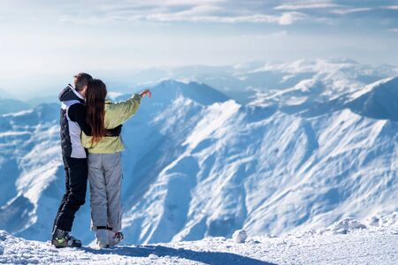Rear view of a loving couple she pointing to snowy mountain range on the ski resort Gudauri