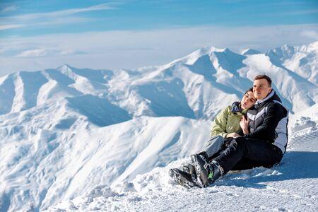 Umarmendes Paar, das auf Schnee sitzt und in der Landschaft auf dem Berg genießt