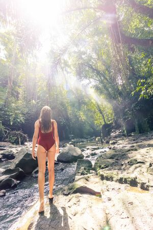 Woman enjoying canyon hidden in jungle in Bali, Indonesia. Slim body and swimsuit, fashion model.