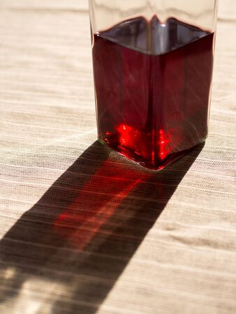 Bottle with red liquid and its shadow