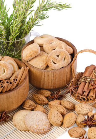 sweet sugar cookies in wooden containers with cinnamon sticks, almonds, anise asterisks, and a pitcher of rosemary photo