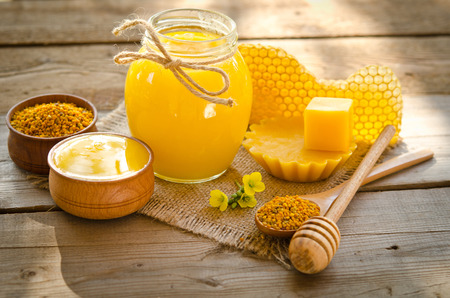 two wooden bowls one with honey another with pollen.The bank of honey stay near honeycombs,wax,wooden spoon with honey and dipper Foto de archivo