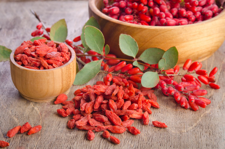 Barberry and dry goji berries in bowls on wooden background Stockfoto