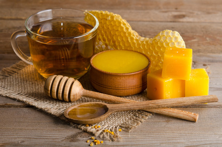 Still life of cup of tea,  honey, honeycombs, wax and pollen granule on wooden background