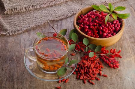 goji: goji fresh antioxidant tea in glass cup and barberries in wooden desk Stock Photo