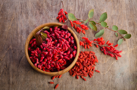 tibet bowls: Barberry in bowl with leaves and dry goji berries on wooden background