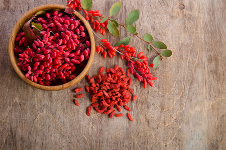 goji: Barberry in bowl with leaves and dry goji berries on wooden background