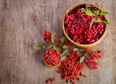 Barberry and dry goji berries in two bowls on wooden background. top view