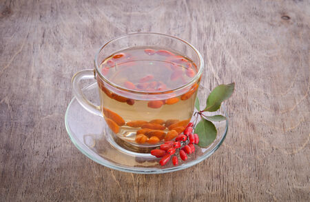 barberries: goji fresh antioxidant tea in glass cup and barberries on wooden desk