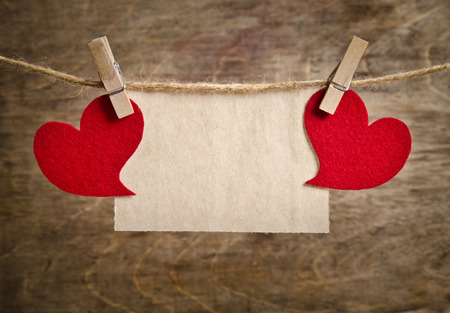 pack string: Two Red fabric hearts with sheet of paper hanging on the clothesline on two clothespins . On old wood background. Stock Photo