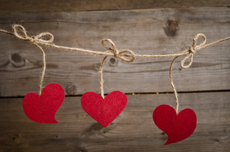Three Red fabric hearts hanging on the clothesline . On old wood background. photo
