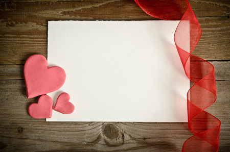 piece of paper lying with hearts and ribbon on a wooden background photo