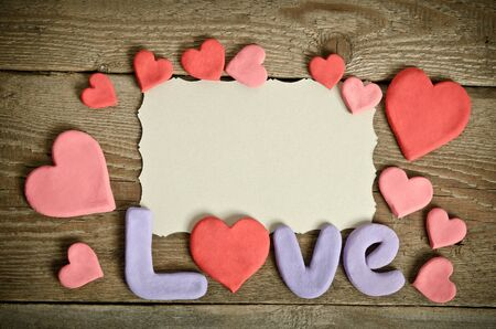 Word Love composition on the wooden board surface and many hearts handmade around. Letters and hearts made from salt dough photo