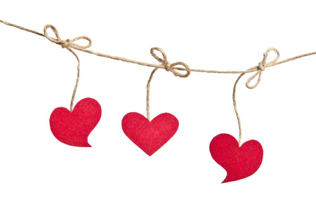 Three Red fabric hearts hanging on the clothesline isolated on white background. photo