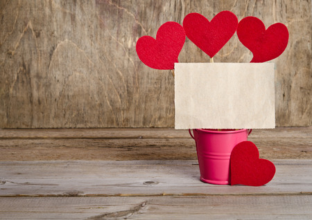 reciprocity: handmade skewers with cloth hearts and piece of old paper for guests for celebration of St. Valentines Day on wooden background