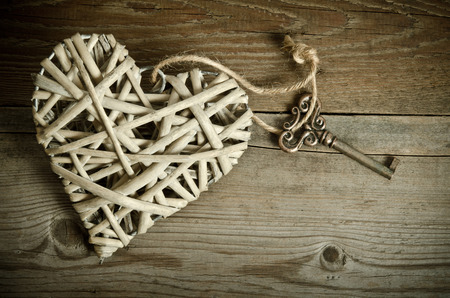 reciprocity: wicker heart handmade with the key lying on a wooden base . top view