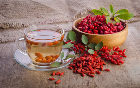 barberries: goji fresh antioxidant tea in glass cup and barberries in wooden desk Stock Photo