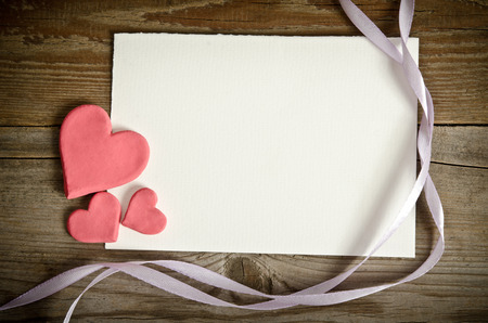 the piece of paper lying with hearts and ribbons on a wooden background photo