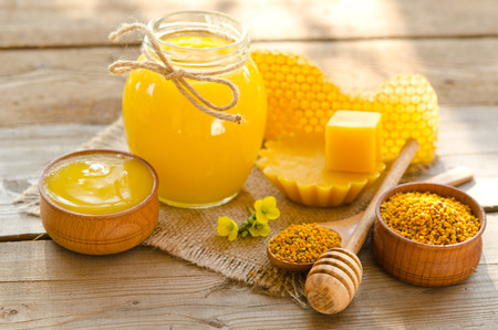 two wooden bowls one with honey another with pollen.The bank of honey stay near honeycombs,wax,wooden spoon with honey and dipper Archivio Fotografico