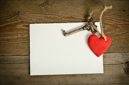 Handmade Heart with key together lying on the paper for message on wooden  table photo