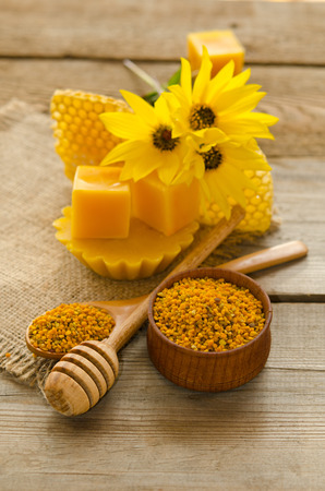 Still life of wax, honeycombs,flawers and pollen granule on wooden background Stock Photo