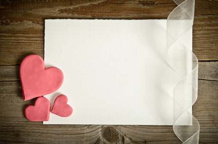 the piece of paper lying with hearts and ribbon on a wooden background photo