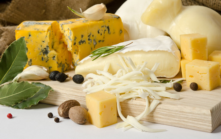 Verschillende soorten kaas met kruiden op de houten raad Stockfoto