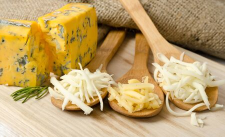 scamorza cheese: Grated cheese in wooden spoons Stock Photo