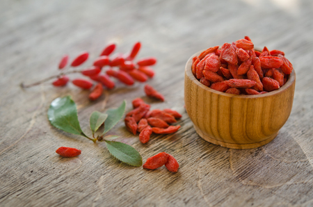 barberries: barberries near goji berries heap and wooden bowl with goji on wooden background
