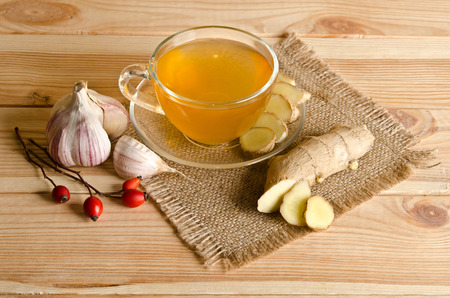 garlic cloves: Cup of tea , ginger, garlic. Home antimicrobial therapy Stock Photo