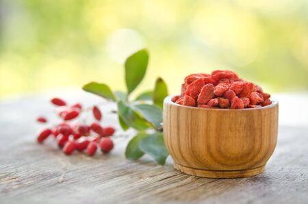 barberries and goji berries isolated on wooden table.