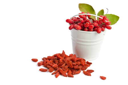 barberries: metal bucket with barberries near heap of goji berries isolated on white background Stock Photo