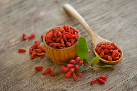 barberries: barberries near goji berries heap and wooden spoon, bowl with goji on wooden background Stock Photo