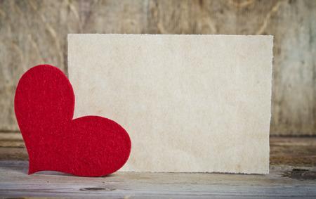 carta de amor: la forma de una tarjeta en el fondo de madera. corazón hecho a mano de fieltro rojo está en la esquina izquierda de la forma